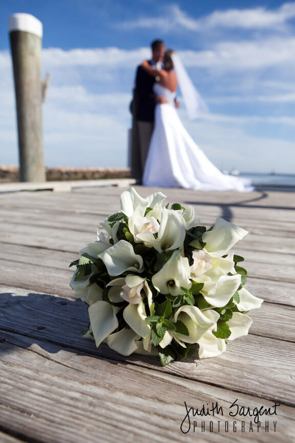 Bridal bouquet on dock with bride and groom in background